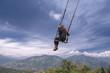 Unknown person swinging at the La casa del Arbol in Banos de Agua Santa, Ecuador