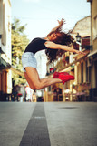 Woman dancer doing a jump on a street in the city