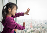 Asian girl is looking out the windows to Tokyo city