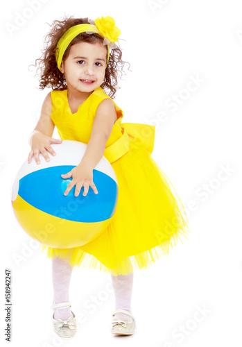 Little girl in yellow dress holding a ball