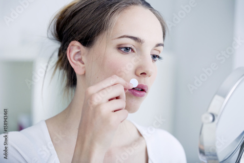 Woman applying a patch to treat labial herpes Poster