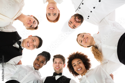 Happy Restaurant Staff Forming Huddle