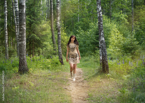 Young girl walking along a path in a forest park