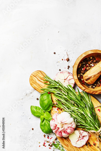 Food background, fresh rosemary, green basil, garlic, pepper on a cutting board, top view