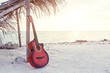 An acoustic guitar standing in the sandy beach under palm tree - 158949688
