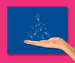 A female hand holding a collection of lightbulbs, bright idea concept with a brightly coloured background.