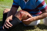 Mid section of rugby player with injured knee