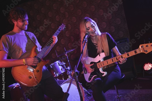 Male and female guitarist performing in nightclub Poster