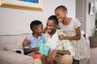 Father and children holding gift box on sofa at home