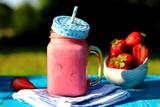 молочный коктейль с клубникой на столе в саду