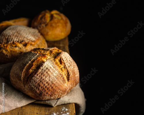 Fresh homemade bread on dark table.