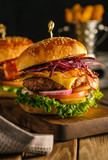 Delicious fresh burger with meat, bacon, cheese and vegetables on a wooden board, in a rustic soul style.