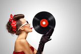 Taste and listen / Beautiful pinup bikini model, licking LP microgroove vinyl record on grey background. - 159077690