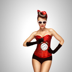 Sexy dream / Sexy pinup girl in a red vintage corset holding a retro alarm clock on grey background.