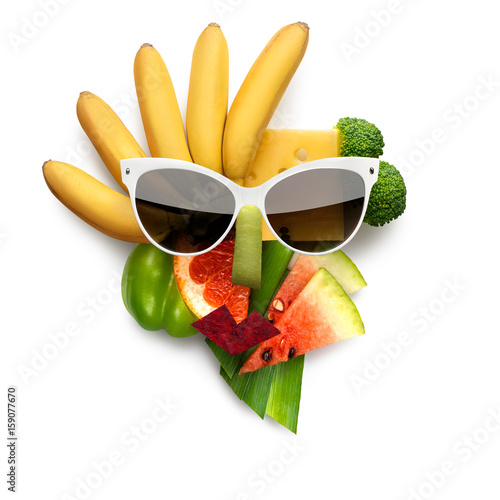 Tasty art / Quirky food concept of cubist style female face in sunglasses made of fruits and vegetables, on white background. - 159077670
