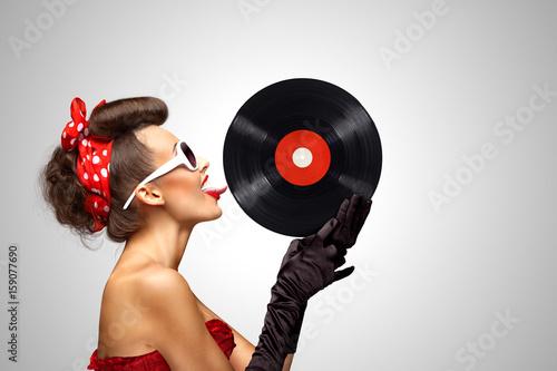 Taste and listen / Beautiful pinup bikini model, licking LP microgroove vinyl record on grey background.