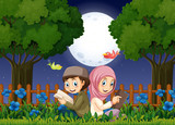 Two muslim kids reading in garden at night