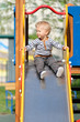 One year old baby boy toddler at playground slide