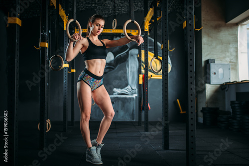 Slim female athlete exercise on gymnastic rings - 159086603