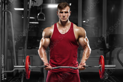 Muscular man working out in gym doing exercises with barbell, strong male