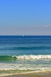 Sailboat sailing at horizon line of the blue waters of Ipanema beach at Rio de Janeiro