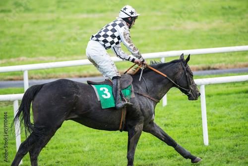 Mud splattered race horse and jockey running on the race track плакат