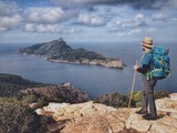 Hiker in the Tramuntana mountains looking at the island of Sa Dragonera, Mallorca, Spain - 159116862