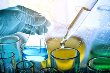 Flask in scientist hand with test tubes background