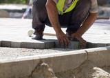 Worker puts sidewalk tile on the road - 159130839