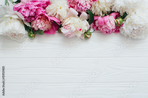 White and pink peonies on a wooden background.
