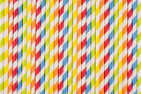 Abstract multicolored rainbow geometric striped background of beverage straw.