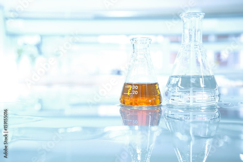 orange liquid and water in flask on science table laboratory