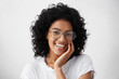 Close-up portrait of Afro American woman with dark curly bushy hair wearing glasses and white top holding hand on cheek looking at camera with shy charming smile feeling enjoyment and shyness