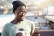 Smiling black African male in glasses and trendy cap tasting delicious coffee and texting friends using cell phone isolated over city blurred background. People, lifestyle and technology concept