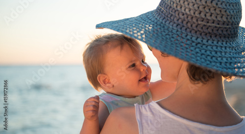 Mother with hat embracing little dougter at beach