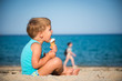 Summer vacation,  cute child eating icecream on beach