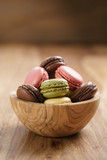 assorted macarons in wood bowl on wooden table, with copy space