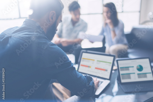 Three partners making research for new business direction.Young businessman working modern laptop and showing documents to young colleague.Business people meeting concept.Blurred background.
