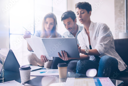 Three young coworkers working on laptop computer at office.Woman holding tablet and pointing on touch screen. Horizontal, blurred background.