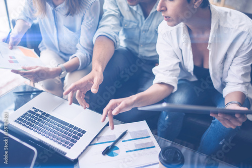 Three young coworkers working on mobile laptop computer at office.Young woman holding tablet and pointing on touch screen. Horizontal, blurred background.
