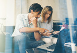 Teamwork concept.Young business people working with new startup project.Woman holding smartphone in hand and man pointing to touch screen.Blurred background,visual effect.Horizontal.
