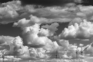 Black and white photos of building cranes against the background of clouds