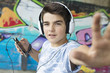 child with headset and phone on the street listening to music