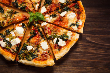 Pizza with feta cheese and spinach on wooden table