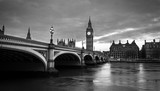 Big Ben and Westminster bridge in London at dusk. Black and white photo with dramatic sky