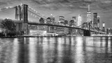 Black and white photo of Brooklyn Bridge and Manhattan at night, New York City, USA.