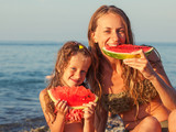 Child with mother eating watermelon