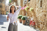 attractive woman tourist with hat in old italian town - 159235031