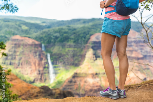 Hiking hiker girl at Waimea Canyon Kauai looking at Waipoo falls Hawaii waterfall. Kauai travel. - 159248843
