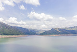 Landscape of natural dam mountain and water reservoir under cloudy sky, natural irrigation system.